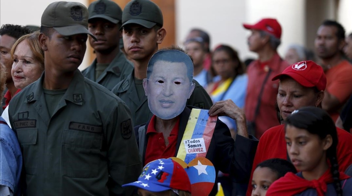 Un seguidor de Maduro lleva una máscara con la imagen del desaparecido Hugo Chávez, en la conmemoración del tercer aniversario de su muerte, en Caracas, el 5 de marzo.