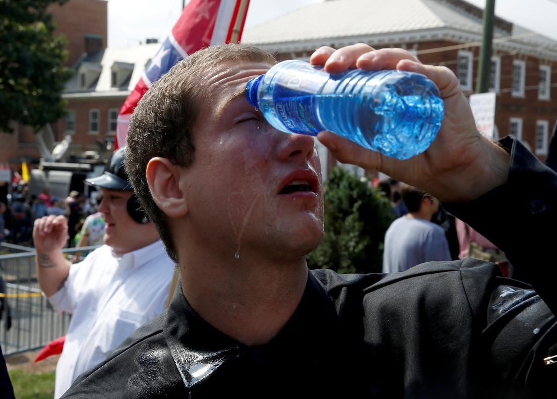 Un manifestante se echa agua en los ojos tras ser rociado con espray pimienta.