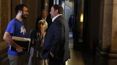El vicepresidente del Govern, Oriol Junqueras, y el diputado de la CUP Albert Botran conversan en los pasillos del Parlament.