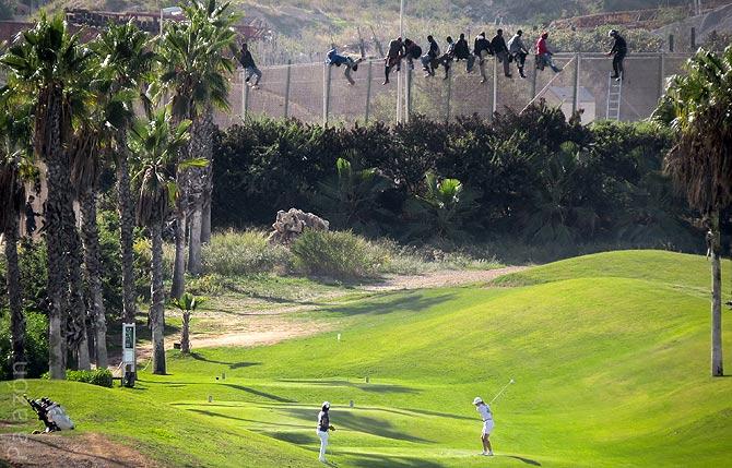 GOLF JUNTO A LA VALLA. Dos jugadoras practican deporte a pocos metros de la frontera de Melilla, donde están encaramados varios inmigrantes.