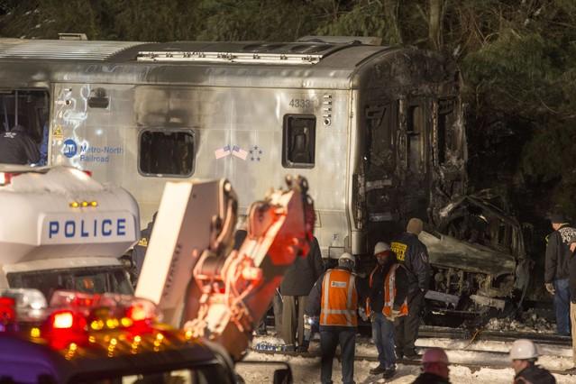 Los servicios de emergencias, ante la locomotora del tren y el vehículo, totalmente calcinado, en Valhalla (Nueva York).