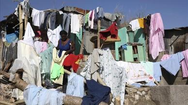 Haitians damnificats pel pas de l'huracà 'Matthew'estenen al sol la roba, an Jeremie (Haití).