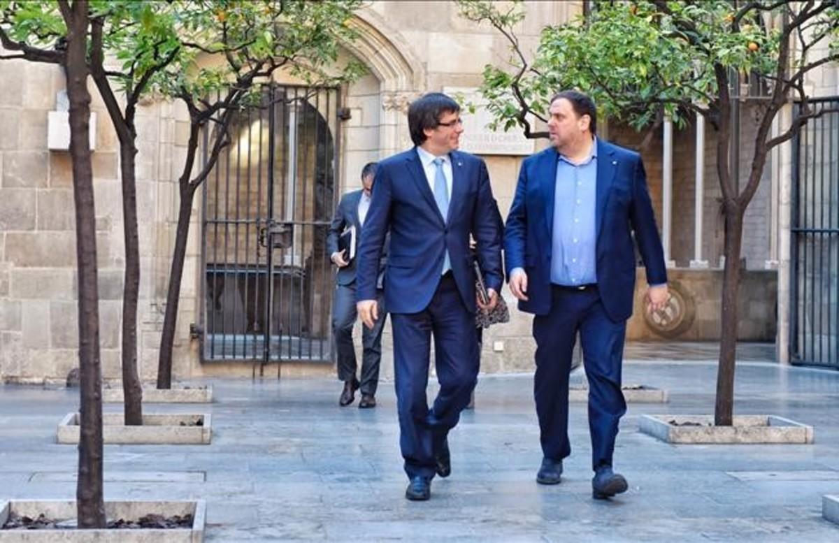 El president Carles Puigdemont y el vicepresidente Oriol Junqueras, este martes, dirigiéndose a la reunión del Govern.