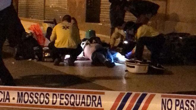 Los vecinos intentan reanimar al conductor del robo en una panaderia en Barcelona.