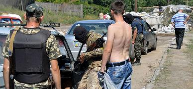 Soldados prorrusos inspeccionan un veh�culo en un puesto de control en la ciudad de Lisichansk, en Ucrania.