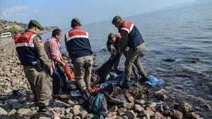 La policía turca traslada el cadáver de un refugiado tras un nuevo naufragio en el Egeo.