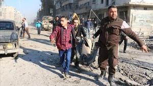 Varios sirios llevan el cuerpo de una víctima tras un bombardeo del régimen sirio en una área controlada por los rebeldes en Alepo, este lunes.