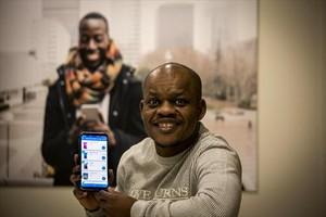 <b>USUARIO.</b> Musa Bala, nigeriano, muestra un móvil con la aplicación.