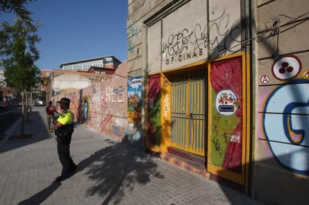 Agentes de los Mossos d'Esquadra custodian la nave industrial desalojada, este jueves, en la calle Almogàvers.