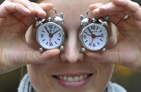 Una empleada del fabricant de rellotges Carlton amb dos despertadors de l'empresa, aquest divendres a Munic, per recordar el canvi d'hora.