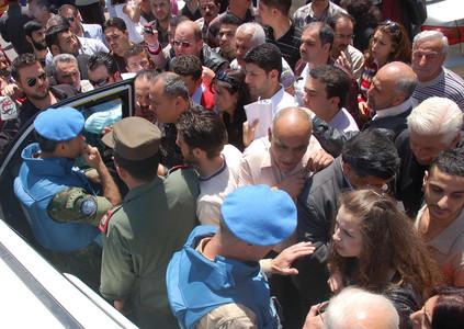Observadores de la ONU, acompañados por soldados del régimen, hablar con civiles sirios, el lunes en la ciudad de Homs.