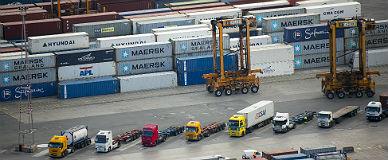 Camiones ante contenedores de carga en el puerto de Barcelona.