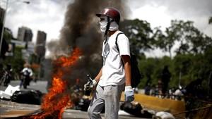 Un manifestante frente a una barricada durante la huelga, en Caracas, el 26 de julio.