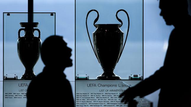 Dos hombres conversan junto a las copas de la Liga de Campeones y la Liga Europa, en la sede de la UEFA en Nyón (Suiza)