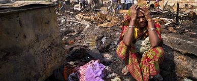 Una mujer india llora al comprobar que una bolsa con dinero para la dote de su hija se ha quemado en un incendio en Gurgeon.