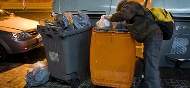 Un joven busca comida en un contenedor en Barcelona.