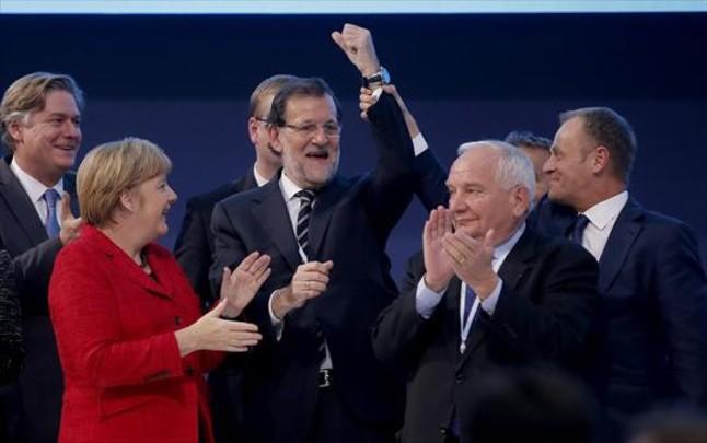 El presidente del Consejo Europeo, Donald Tusk, levanta el brazo de Rajoy en presencia de Angela Merkel y otros dirigentes populares europeos.