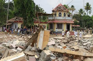 People stand next to debris after a broke out at a temple in Kollam in the southern state of Kerala