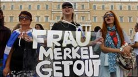 Tres mujeres sostienen una pancarta contra Merkel, este martes en el centro de Atenas.