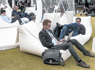 Asistentes al Mobile World Congress descansan en una zona al aire libre del recinto de Gran Via