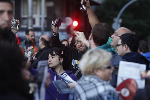 Diversos veïns sacsegen el clauer durant la protesta a la plaça de Sants, aquest divendres.