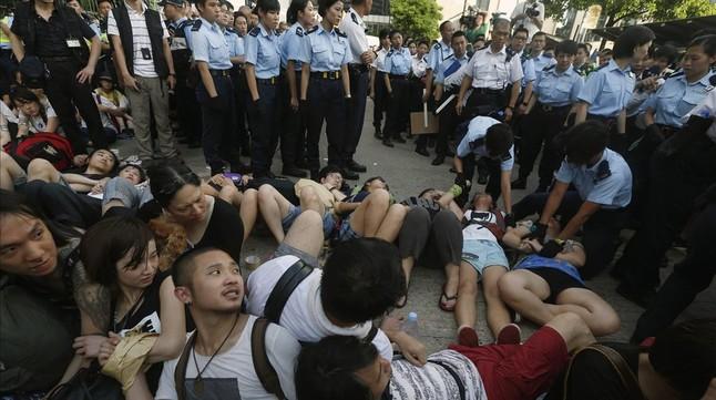 Participantes en la sentada unen sus manos para evitar ser detenidos, este miércoles en Hong Kong.