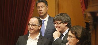Puidemont, junto a Turull, sonr�e, observados por Albiol, este mi�rcoles en el Parlament.