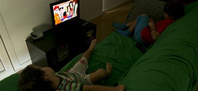 Dos ni�os miran un cap�tulo de una serie de dibujos animados en la televisi�n, este jueves.