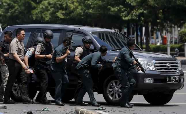 Agentes de policía se protegen tras un coche, durante el enfrentamiento con los asaltantes.