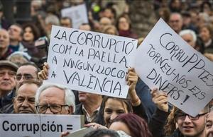 Asistentes a la manifestación contra la corrupción celebrada este domingo en Valencia portan carteles contra el PP y los casos que han afectado a esta comunidad.
