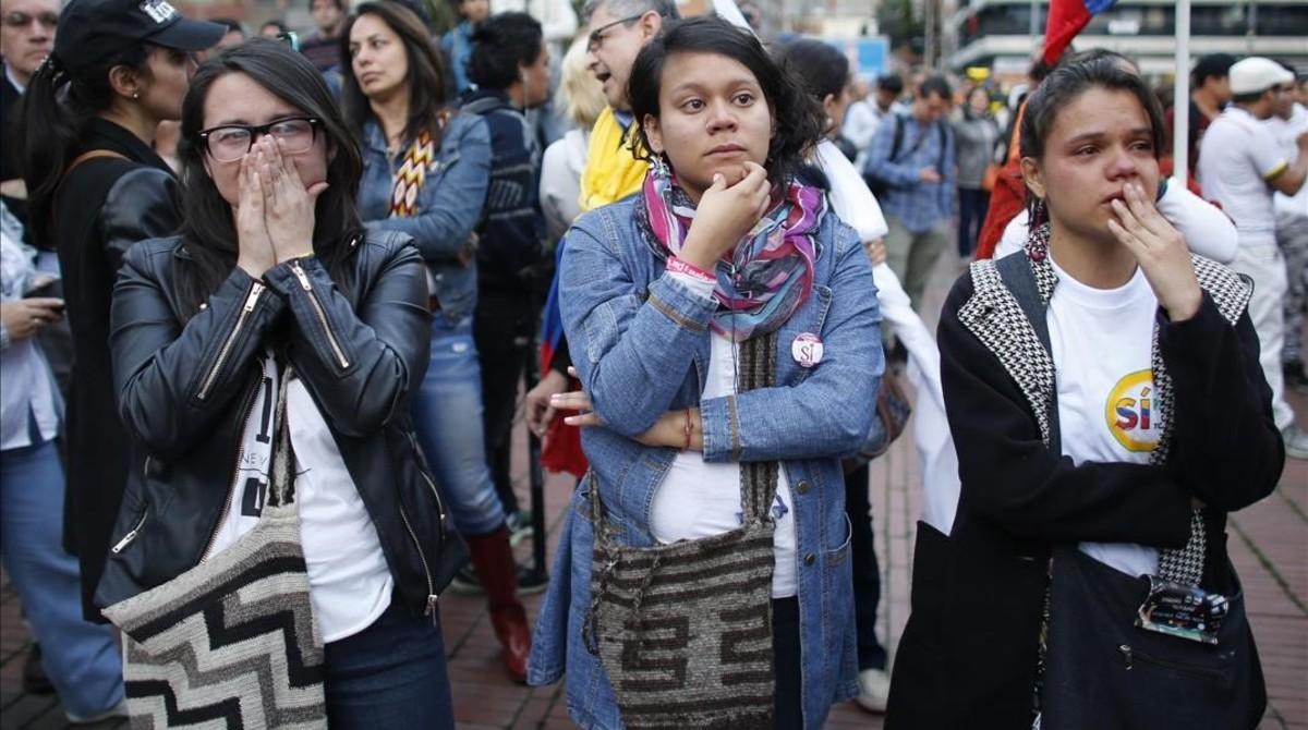 Partidarios del acuerdo de paz siguen los resultados del escrutinio en una pantalla gigante, en Bogotá, este domingo.