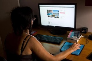 Una mujer consulta la plataforma on line Airbnb.