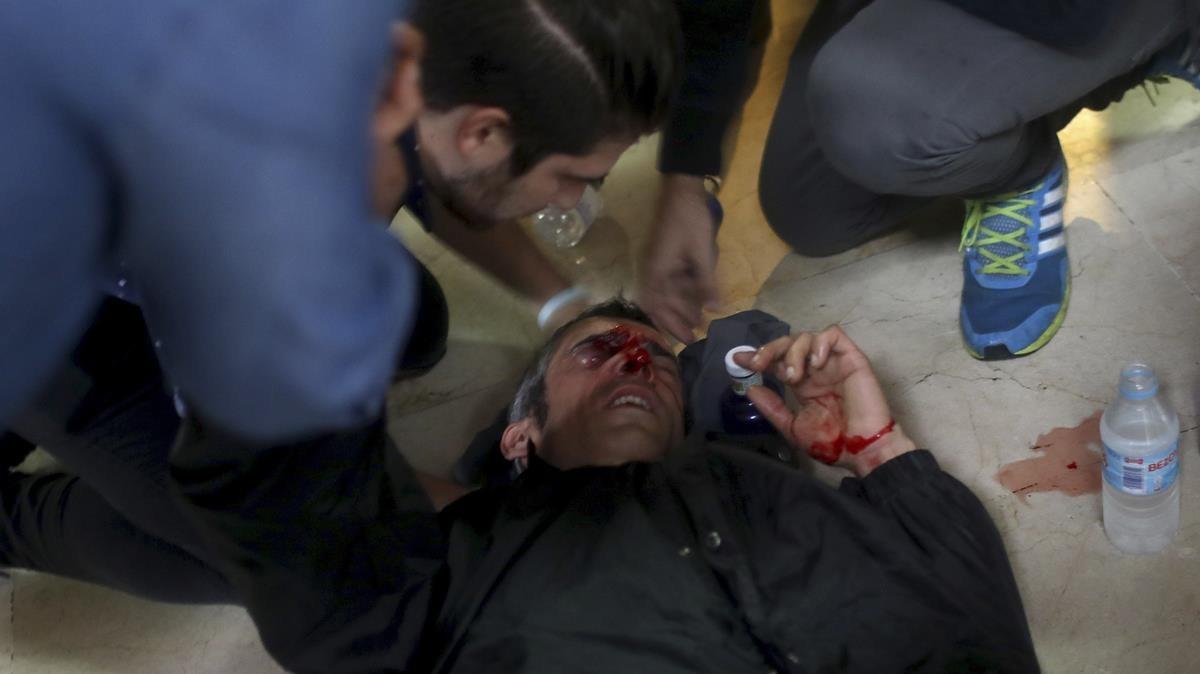 Un manifestante es atendido después de ser golpeado por una bala de goma disparada por la Policía Nacional de España cerca de la escuela Ramón Llull