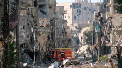 Un camión de bomberos abandonado entre los edificios destruidos por los bombardeos en Deir Ezzor, en una imagen de archivo, en septiembre del 2013.