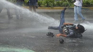 La fotógrafa Ariana Cubillos es derribada por un chorro de agua de un vehículo antidisturbios enuna manifestación del sector sanitario en Caracas, Venezuela.