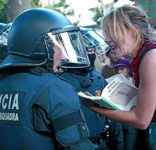 Una manifestante con un libro protesta ante un mosso, el pasado 15 de junio frente a la Ciutadella.