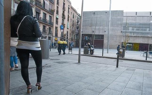 Una prostituta observa el pas de dos guàrdies al carrer den Robador, davant la Filmoteca, el març passat.
