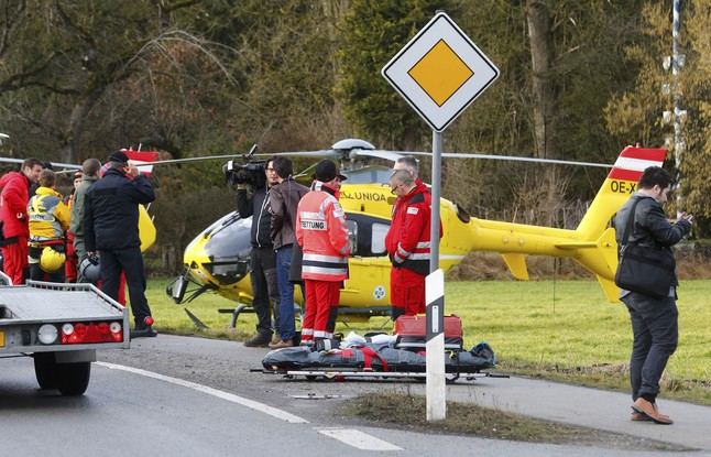 Rescuers and journalists stand in front of a rescue helicopter near Bad Aibling