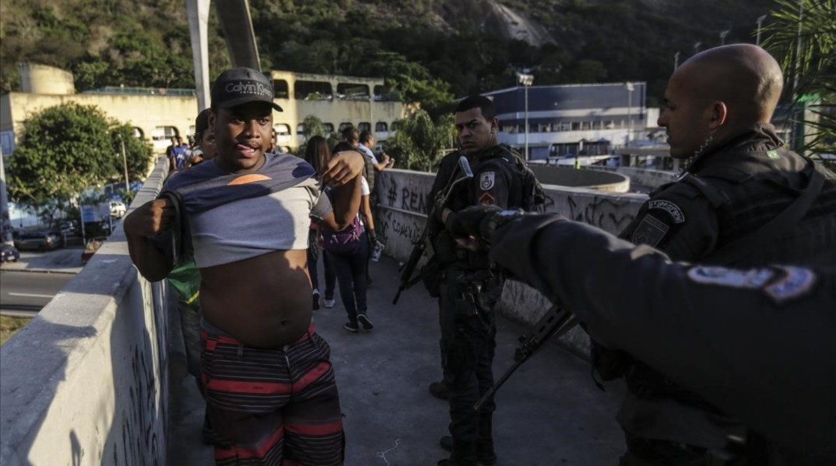 Agentes de la policia patrullan frente a la favela Rocinha durante una marcha de los habitantes pidiendo paz, el jueves 19 de octubre de 2017 , en Río de Janeiro, Brasil.