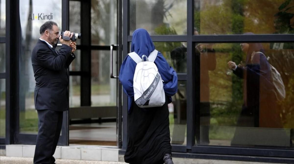 Un miembro de la escuela musulmana de secundaria Al Kindi filma a una estudiante mientras entra en el centro educativo en Decines, cerca de Lyon (Francia).