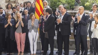 El 'president' Carles Puigdemont, junto a su Govern, en el anuncio de la fecha y la pregunta del referéndum, en el Palau de la Generalitat.