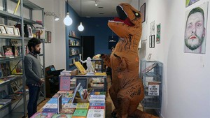 Kike García, la meitat d'El Mundo Today, davant d'un T-Rex aïrat, en la nova llibreria-galeria d'humor La Llama.