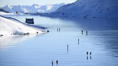 """Visitantes disfrutan de un día soleado en el """"hielo negro"""" del Lago Bianco, en Poschiavo, Suiza."""