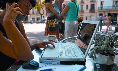 Una mujer consulta internet en un port�til mientras conversa por m�vil, en una terraza de Barcelona.