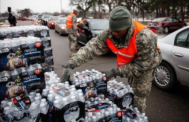 Efectivos de la Guardia Nacional reparten agua embotellada a los habitantes de Flint.