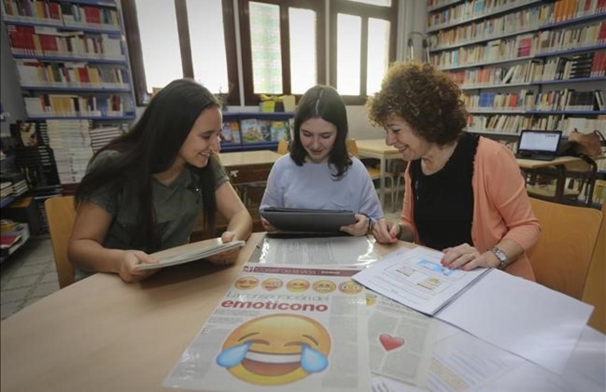 Salma Zian (a la izda.), Cristina Manzanares y la profesora María del Pilar Menoyo, con la portada que inspiró su trabajo de investigación, en la biblioteca del instituto Juan Manuel Zafra de Barcelona
