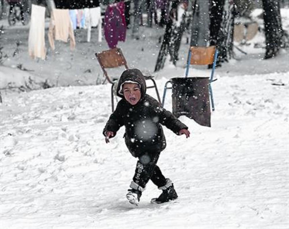 Un niño sirio, en un campo de refugiados lleno de nieve cerca de Atenas.