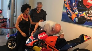 Toni Salom, abuelo del fallecido joven piloto mallorquín, besa, entre lágrimas, la moto de su nieto Luis, en la inauguración hoy de una exposición en Palma.