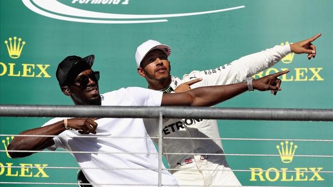 Lewis Hamilton celebra su victoria con Usain Bolt en el podio de Austin.