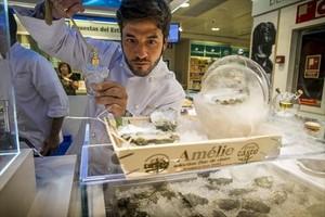 Un cocinero vaporiza una ostra con vodka mientras al lado se ahúma otra con madera de castaño, en el la barra de ostras Amélie de El Corte Inglés de plaza de Catalunya.